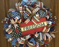 This beautiful bright bold patriotic wreath is made on a wired work wreath form using a red 21 wide deco mesh as its base and layered comes made from blue and white 10 wide deco mesh, 2 and a 1/2 inches wide Patriotic deco mesh ribbon, 5 different styles of wired patriotic ribbon, glittered red, white, blue and silver styrofoam stars, and a land of the free wooden sign. The wreath measure 24 wide and 8 in depth. This wreath is made and ready to ship. Feel free to message me any questions you…