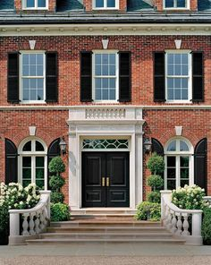red brick with black shutters-I like the rounded black shutters for the curved windows and the white stone keys above the windows- this would work for our house