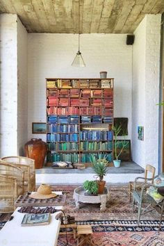 Moroccan rugs and small table compliment the colour coded book display #home decor