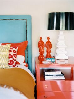 a bright blue headboard and orange nightstand, accessorized by a black and white lamp and two orange mini-statues
