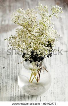 Vase with bunch of Gypsophila (Baby's-breath flowers) on white wooden table by Larina Natalia, via ShutterStock