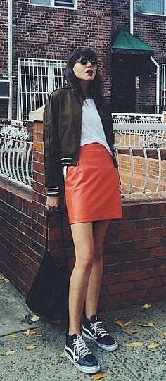 A bomber jacket with leather skirt and sneakers.