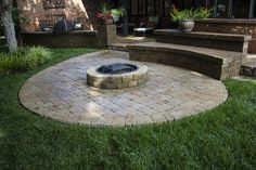 Curvilinear patio with a stone bench and small stone fire pit by Red Valley Landscape & Construction in Edmond, OK.