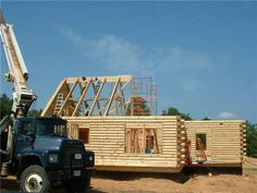 This photo from Satterwhite Log Homes shows the trusses being lifted on site.