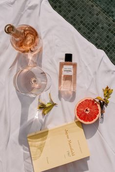 Summer flat lay with drinks, fruit, books, and perfume.