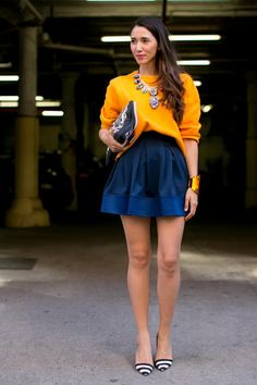 Da New York outfit super fashion con felpa arancio, mini blu, e maxicollier in cristalli