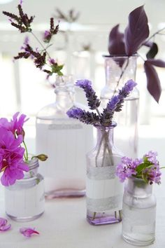 Lavender-colored flowers in different-sized jars, good if the table will have ivory tablecloth, lavender flowers and possibly pink accents