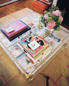 Elizabeth Bauer Photo - A Lucite coffee table covered with books and a vase of flowers
