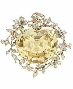 J.E. Caldwell & Co., spilla/ciondolo in oro con uno zaffiro giallo al centro e diamanti a contorno, 1900 ca.