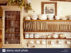 Stock Photo - Close-up of cream bowls on wooden plate rack beside small wall cup. - Stock Photo – Close-up of cream bowls on wooden plate rack beside small wall cupboard in cottage k - Wooden Plate Rack, Plate Rack Wall, Plate Shelves, Plate Storage, Wooden Plates, Plates On Wall, Wall Mounted Dish Rack, Wooden Dish Rack, Storage Racks