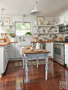 This small country kitchen certainly doesn't lack rustic charm. White cabinets topped with wood countertops and a beaded-board backsplash lay a solid foundation. The farmhouse sink and barn-style ligh Small Country Kitchens, Country Kitchen Designs, Modern Farmhouse Kitchens, Rustic Kitchen, New Kitchen, Home Kitchens, Kitchen Decor, Kitchen Ideas, Kitchen Country