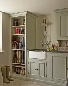 This organised utility room is decorated in a netural colour and have plenty of clever storage. The room is fitted with bespoke blue grey painted cabinetry that ensures there is little clutter on the floor.