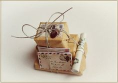 Miniature mail packages: maybe use clay for the boxes, wrap in thick envelope paper, print out some miniature post cards, wrap all in twine and put into miniature bottle? Want to re-create this and will have a tutorial up soon on my blog. Did you say blog?