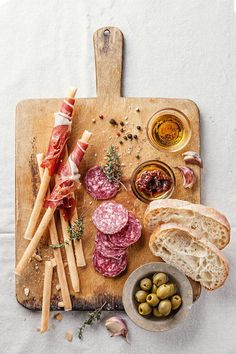 Italian Appetizer Board, No need for a recipe. Grissini Breadsticks wrapped in Prosciutto, Hard Salami, Green Olives, Olive Oil, Sun Dried Tomatoes in Oil, Roasted Garlic, and a loaf of Ciabatta.