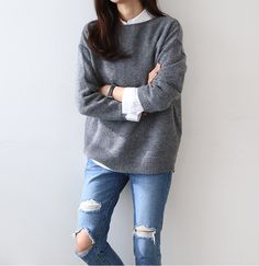 Oversized grey sweater, white blouse, ripped blue jeans.