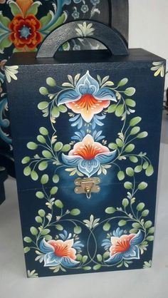 Beautiful Rosemaling has been used to decorate this case. The pale colours really stand out on the navy background. Lovely example of Folk Art