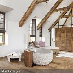 Eine freistehende Steinbadewanne in einem tollen Bad mit Kalkputz an den Wänden …