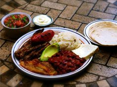 Grilled meat and pork sausages, stewed beans, chismol, fried plantain, and rice. These are served with sour cream, white fresh farmer's cheese, avocado and