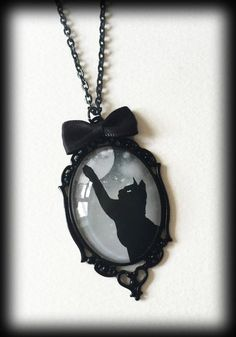 A gothic witchy glass cameo necklace featuring a black and grey image of a black cat reaching for the moon with a black starry background. Set in a black metal filigree oval frame and finished with a little black satin bow. Comes on an 18 inch black chain with a 3 inch extender.  The necklace measures 65mm high x 35mm wide.  Lead and nickel free.  As with many of my other pieces, this item can be customized. For example, a necklace can be made into a brooch, smaller necklaces can be made…