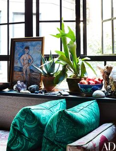 Pillows in a malachite-patterned fabric sit on a bench in the bedroom. The painting is a flea-market find.