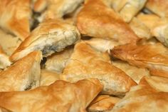 Little bites of heaven! My super tasty traditional Greek spanakopita triangles recipe, perfect for every time of the day as delicious starter, light snack or finger food dinner! Discover how to make it to perfection here...