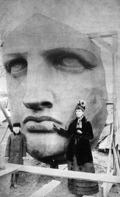 People posing next to the Statue of Liberty as it's unpacked. (1886)