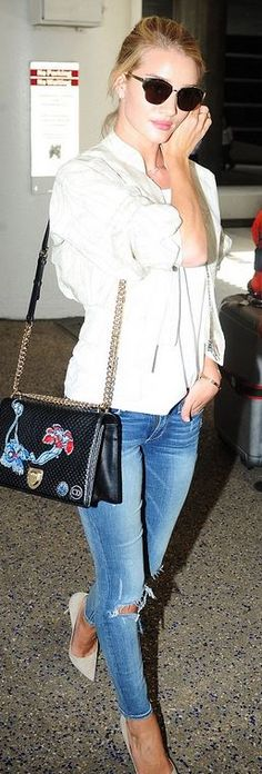 Who made  Rosie Huntington-Whiteley's white jacket, black print handbag, cat sunglasses, gold jewelry, nude suede pumps, top, and blue ripped jeans?
