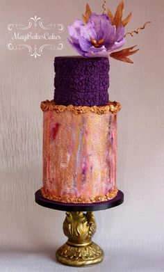 Gold and violet cake. silicone mould at the top tier and sides of the cake. The bottom tier is made of cake lace for textured effect and hand-painted.