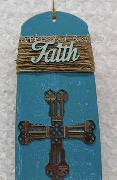 Blue inspirational wooden Faith sign made from a repurposed ceiling fan blade and house/car keys. * Natural jute embellishment * Wooden Faith wording * Blue distressed background painted with interior house paint * Recycled house keys laid out in a cross pattern Length: 20.5
