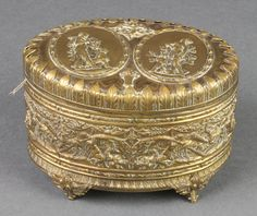 "Lot 195, An oval Continental embossed gilt metal trinket box, the lid decorated figures an archer, raised on 4 panelled supports 3"" x 5"" x 3 1/2"", est £40-60"