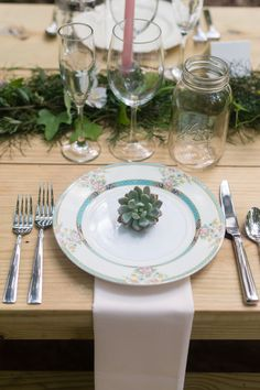A woodsy wedding place setting with mismatched china and a succulent on each plate.