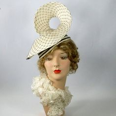 This attractive straw hat is made from a vintage white straw hood from Switzerland and vintage black veiling. The accents on the hat include vintage black straw braiding and vintage black veiling. Hand formed and hand sewn. The hat fits lightly onto the head and the cosmic swirl is worn with the curve at the top center of the forehead. Fits head sizes 22 1/2 to 23 1/4 comfortably. It has an elastic band which can be worn under the hair and around the back of the head. There is also...