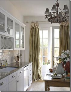 French Style - Karyl Pierce Paxton - New Orleans Cottage - White kitchen with a Louisiana wood table and soft drapes dressing the French doors. French Door Curtains, French Doors, Burlap Curtains, Hanging Curtains, Drapes Curtains, Kitchen Dining, Kitchen Decor, Kitchen Ideas, New Orleans Homes
