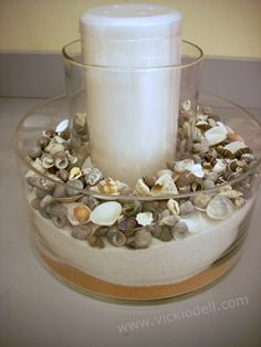 clear cylinder vase, sand, sea shells, candle