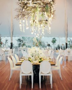 Lights, wooden branches, and orchids twinkle above the head table