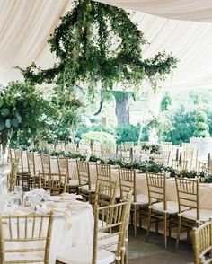 A Dreamy Garden Wedding in Nashville, Tennessee | Martha Stewart Weddings - Linley Stokes designed the reception tent, which overlooked the club's golf course. Champagne-colored drapery and endless greenery created a lush feeling, meant to mimic moss that cascades from Southern trees. A large, crystal chandelier (the biggest Margaret could find in the area) was covered in greenery and moss from Vintage Florals.
