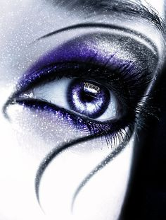 Silver and purple shimmer eyeshadow around eyes. Black swirl eyeliner. Fantasy makeup