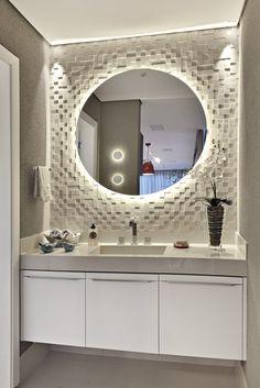 A iluminação atrás do espelho do lavabo cria um jogo de luz e sombras no mosaico e na bancada ambos de porcelanato