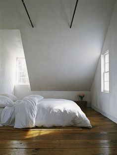 Sparse room. This minimalism works because of the beautiful floor and the architecture of the space.  Could work in an attic under a slanted roof with windows like this.