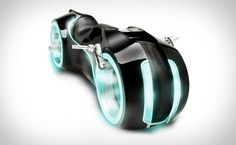 It's not the first movie-inspired ride we've seen, but it's definitely one of the coolest. The Tron Legacy Lightcycle is built to be street-legal, and features a 4-stroke Suzuki engine, a 6-speed constant mesh manual transmission, hubless wheels, custom tires, a padded leather seat, a hardened steel frame with a fiberglass body, and electroluminescent strips on the body, rims, and cowlings for that glowing neon look the film is known for.