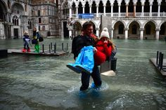 A man carries a young girl through the flooded Piazza San Marco, on November 1, 2012 in Venice. | www.theatlantic.com | Photo: Olivier Morin/AFP/Getty Images