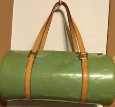 Louis Vuitton Vernis Bedford pre-owned patent leather barrel style satchel handbag in a lime green color, with the LV logo throughout. Comes in 13 inches wide by 7.5 inches high, with a light tan colo