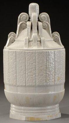 Manufacture nationale de SÈVRES Rare pot couvert en porcelaine émaillée gris perle à corps cylindrique, talon plat de forme octogonale à décor de motifs floraux et de stries. Le couvercle présente un décor d'enroulements striés en chutes. Cachet en creux de la Manufacture de Sèvres, lettre date «G» pour 1926 et monogramme «E.R». H: 25,5 cm