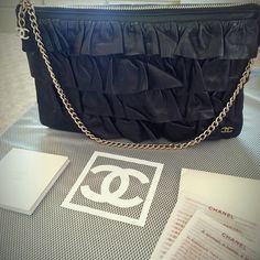 """Rare Authentic Chanel Black Lambskin Ruffle Purse Temporary sale! Brand new. RARE. 100% authentic CHANEL handbag. Comes with Chanel envelope with care/information card & grey Chanel dust bag. Crafted of tiers of ruffled luxurious black lambskin leather. Features gold hardware chain that can be used as a shoulder or wrist strap (9"""") & a top Chanel CC logo on the chain zipper pull that opens to a satin interior. Satin interior has a couple tiny minor marks as seen in the 3rd & 4th photograph…"""