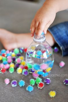 """homemade """"glitter wands"""" // Fill a bottle half full with water, have your kid help you stuff it with small sensory items: balls, pompoms, ribbons, paperclips, foam shapes, beads, etc. Then seal bottle with glue, let dry. Shake and play!"""