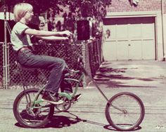 A young Bill Gates riding his bike.