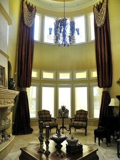"""Two Story Elegant Drapes with drapery swags, mounted on 9"""" long iron medallions.  Drapes fall into a bishop sleeve at the cuff."""