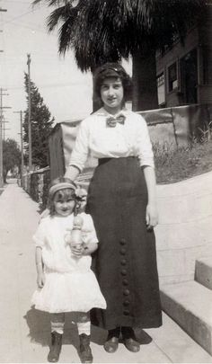 Little girl holding her Kewpie doll; pictured with her mother. Circa 1918.