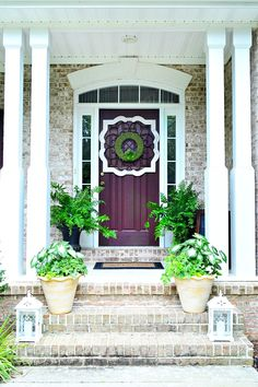 The framed greenery wreath makes this front porch feel so welcoming and full of color! Click through for more inspiration from Heather of At The Picket Fence. || @meetuatthefence