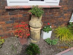 "Old chimney pots (and a bead bin!) used as garden features. I believe this is known as ""upcycling""."